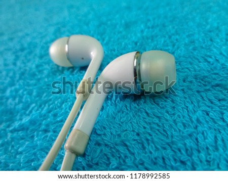 Earphone or Earphones on blue background, white earphone or earphones for listen digital music on smartphone or other electronics gadgets.