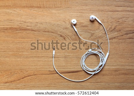 Earphone or earphones on wooden background.the white earphones for using digital music or smart phone | earbuds isolated. Top view.