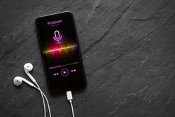 Earphones and mobile phone with podcast app on screen