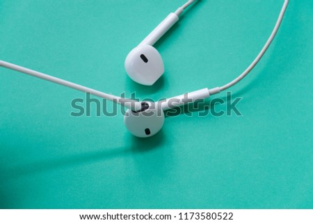 Earphones Cleaning with Cotton Bud on Turquoise Background