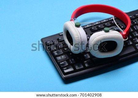 Earphones in red and white color with computer keyboard. Music and call center concept. Sound recording and technology. Headphones and black keyboard. Electronic appliances isolated on cyan background