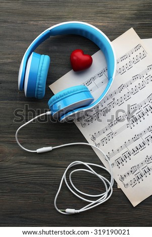 Earphones with red heart and music notes on wooden table close up