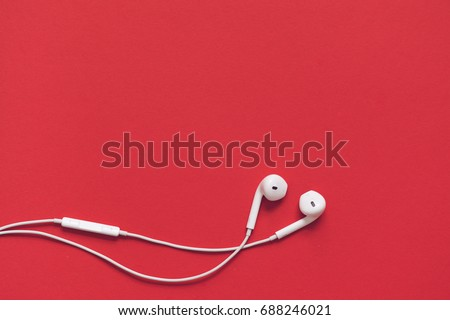 Earphons on red background.