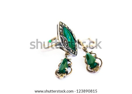 Earrings and ring with green stones isolated on white background.