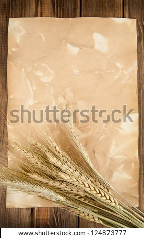 ears of corn of wheat on old paper and wooden table
