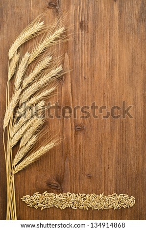 Ears of rye with seeds on wooden background