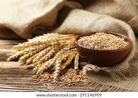 Ears of wheat and bowl of wheat grains on brown wooden background #291146909