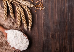 Ears of wheat and flour in the wooden spoon on the table