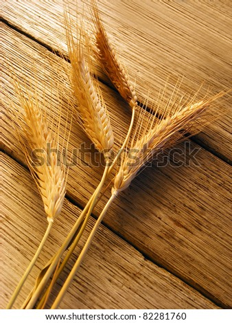Ears of wheat on a wood background. Soft light