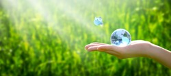 Earth crystal glass globe in human hand and flying butterfly with blue wings on grass background. Saving environment and clean green planet concept. Card for World Earth Day concept.