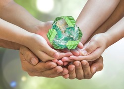 Earth day and ecology concept with family's hands volunteering saving planet with recycle sign. Elements of this image furnished by NASA