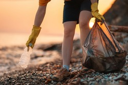 Earth day. Cleanup garbage on the ocean coast. A volunteer with polyethielene bag picking up a plastic bottle on the beach. Close-up. Sunset in the background. The concept of conservation of ecology.