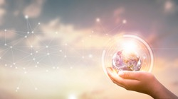 Earth Day concept: hands hold earth and circle global network connection communication on sunset background, Elements of this image furnished by NASA