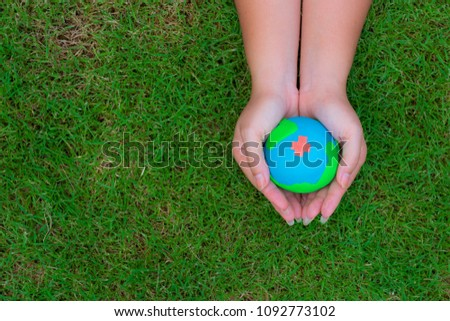 Earth Day concept. Woman hand holding handmade globe on green grass background.