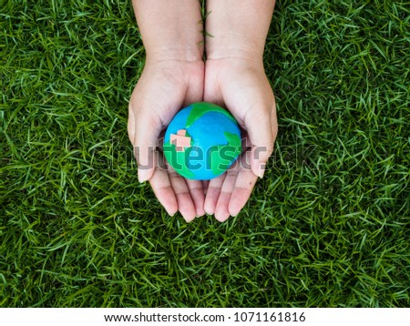 earth day. earth in hands and green grass field background. environment save earth concept. #1071161816