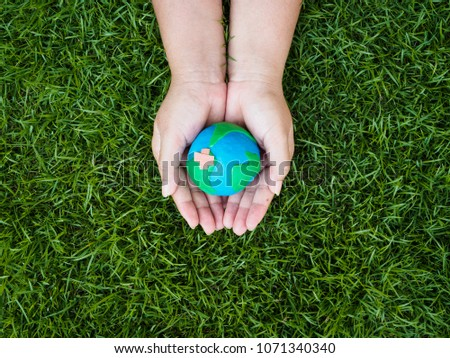 earth day. earth in hands and green grass field background. environment save earth concept. #1071340340