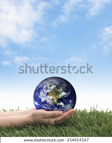 Earth Day. Hands holding earth over grass on a blue sky. The planet earth image provided by NASA.