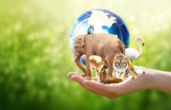 Earth Day or World Animal Day concept. Save planet, protect wildlife nature reserve, protection of endangered species, biological diversity. Elephant, tiger, deer, parrot, flamingo with globe in hand.