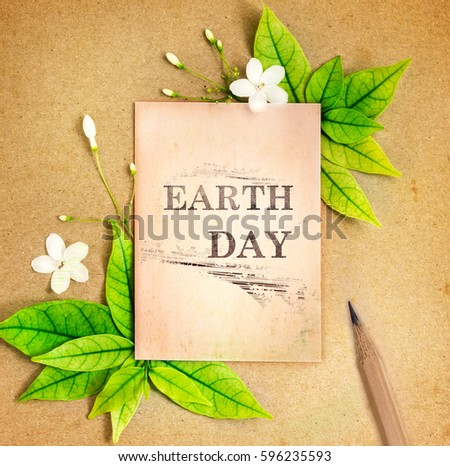 Earth day paper sheet with fresh spring  green leafs and flower border frame on brown recycle paper background , eco natural banner concept