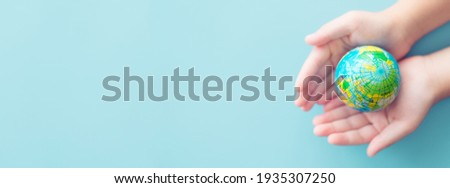 Earth day.World environment day.Kid Hands holding earth globe blue banner background.CSR.Big data research, Discovery, Planet, go green, Earth during coronavirus, hope, vaccine.Climate change.human.