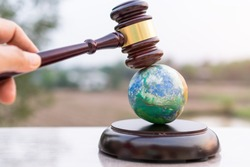 Earth destruction and destroy environmental by hand human concept. Judge gavel / world model should have legal force or certification for survival of all mankind with international Environment law