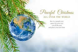 earth globe as Christmas ball hanging in fir branch, message: peaceful Christmas all over the world, symbol, metaphor, copy space, bright snowy background. Elements of this image furnished by NASA.