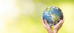 Earth globe in family hands. World environment day concept. Elements of this image furnished by NASA