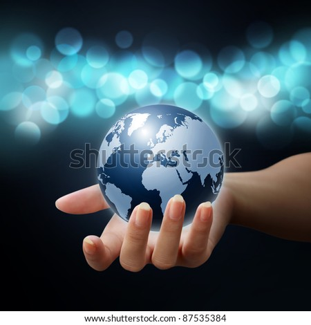 earth globe in woman hands on blue bokeh background - stock photo