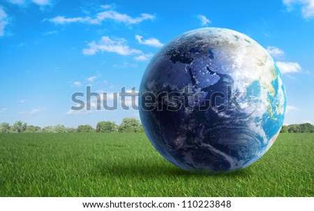 Earth globe on a green  field of grass - stock photo
