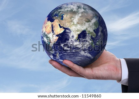 earth in a hand on background blue sky