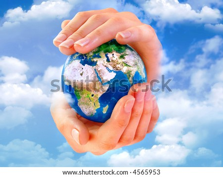 Earth in hands with clouds on the sky