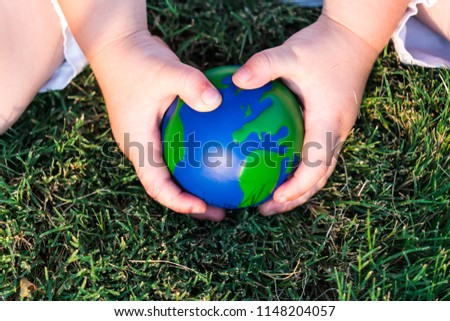 Earth is in our hands now. In the hands of future generations. Small child's hands holding small earth like globe on grass background #1148204057