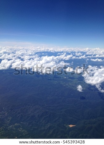 Earth landscape viewed from airplane. Earth surface under the white clouds and blue sky from aerial view. Cloudy weather covering residential land and argriculture land. #545393428