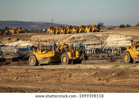 Earth moving equipment at a construction grading site with other tractors lined up in the background