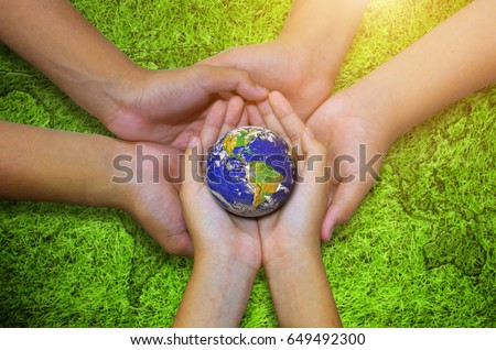 Earth planet in asian Children hand on green grass background. - Elements of this image furnished by NASA