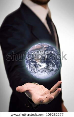 Earth Sphere (furnished by NASA) in the palm of a business man like a magic sphere