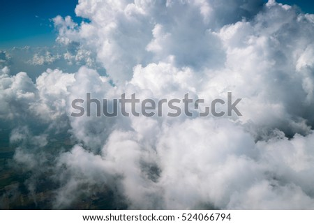 Earth surface landscape viewed from airplane under white clouds and blue sky from aerial view covering residential and agriculture land.