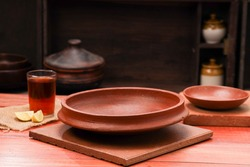 Earthenware, an empty earthenware placed on a square base  with lemon tea  and an empty small earthenware placed beside , wooden texture with kitchen background.