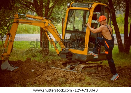 Earthwork concept. Earthwork operator at excavator. Man climb on digger for earthwork. Earthwork and ground work.