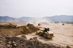 Earthworks in an open area on a summer sunny day. Cargo dump trucks, excavators, wheel loaders and bulldozers operate at the same time.