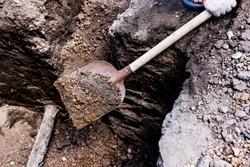 Earthworks. Shovel in the ground in the garden. A bayonet spade in the garden. Digging up the soil on the suburban area. Land works with a trench tool.