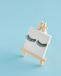 Easel and white canvas with eyelashes on blue background. Creative minimal concept.