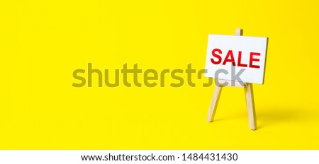 Easel sign with the words Sale. Advertising marketing. Discount. Shopping online. Increase sales and attract new customers. Sale of goods and products by attractive prices and promotions. #1484431430
