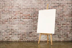Easel with blank canvas on a brick wall background