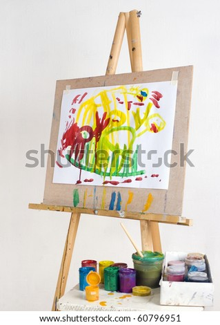 Easel with children's drawings and paint