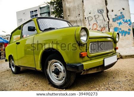 East-German plastic vintage car parked near Berlin wall