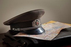 East German Stasi officer cap placed on a map of Berlin, a 1966 DDR document and briefcase.
