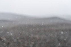 East Iceland barren landscape in summer with abstract background of snowing snow storm flakes falling weather and brown hills mountains