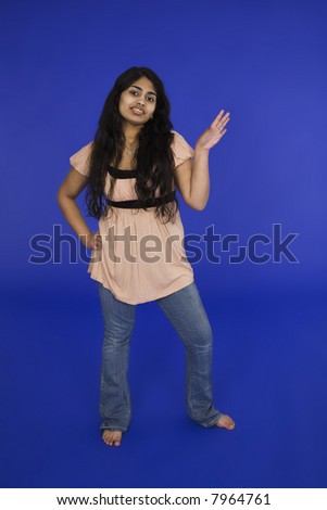 East Indian teenage girl posing on blue background with some attitude ...