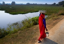 East Indian woman covered in red sari walks to get water for small village.